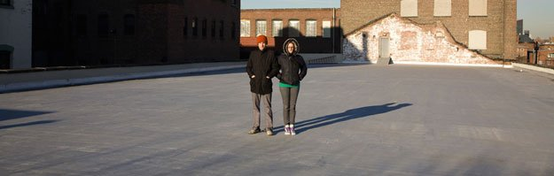 Two people standing on a freshly water-proofed sealed flat roof.